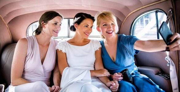 Brud og forlovere tar selfie inne i en flott gammel veteranbil som er leid til bryllupet