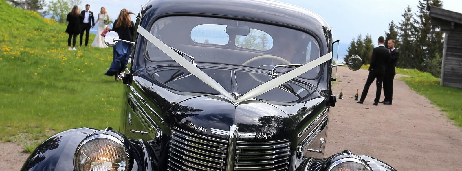 Gammel Chrysler veteranbil venter på brudeparet som tar bilder i bakgrunnen