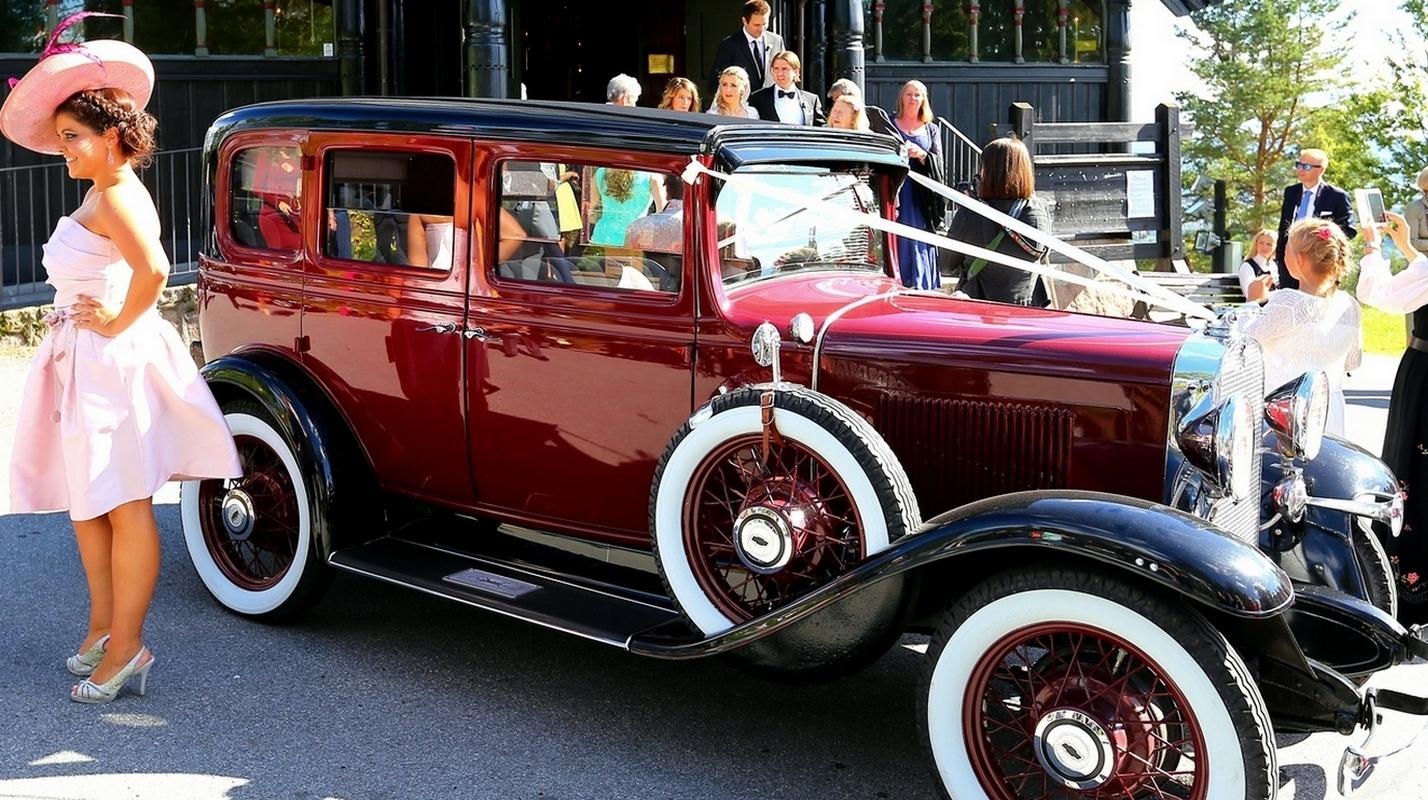 Rød 1930 talls Chevrolet som bryllupsbil utenfor Holmenkollen kapell i Oslo