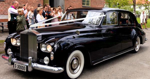 Svart Rolls-Royce Phantom V i bryllupskjøring i Buskerud. Gjester vinker til brudeparet.
