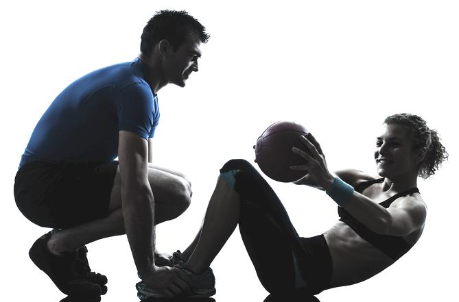 Mannlig personlig trener og kvinnelig kunde som tar sitt-ups