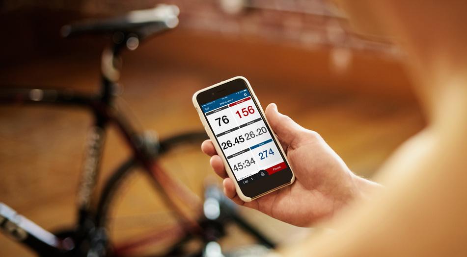 Hånd som viser mobiltelefon med pulsklokke, klar for sykkeltur